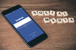 online advertising space gray iPhone 6 with Facebook log-in display near Social Media scrabble tiles