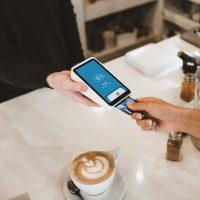 credit card processing fees person putting magstripe card near black card terminal