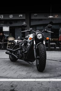 MOT checks black and gray cruiser motorcycle parked beside black concrete building
