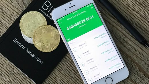 paying with bitcoin silver iPhone 6 beside two coins