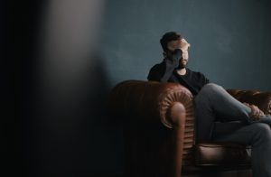 debt problem a man holds his head while sitting on a sofa