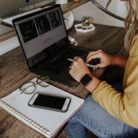 remote worker person in blue denim jeans using macbook pro