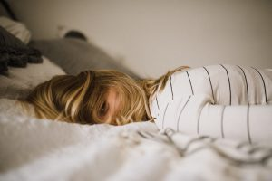 financial stress woman lying on bed