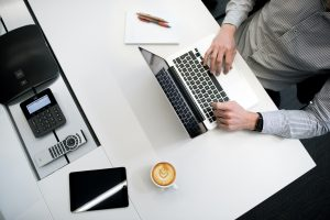 back-office person using laptop on white wooden table