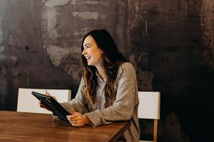 /hiring remote workers woman sitting around table holding tablet