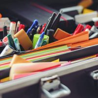 office supplies assorted pen and colored papers in organizer case