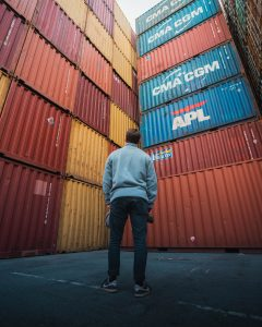 shipping containers man in gray hoodie walking on sidewalk during daytime