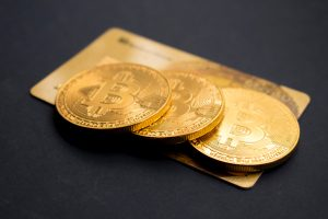 bitcoin investment three round gold-colored Bitcoin tokens