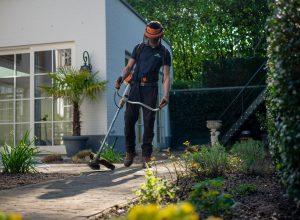 worker man in black t-shirt and blue denim jeans holding shovel