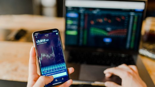 crypto trading person using phone and laptop computer