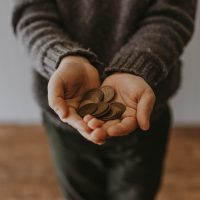 nonprofits copper-colored coins on in person's hands