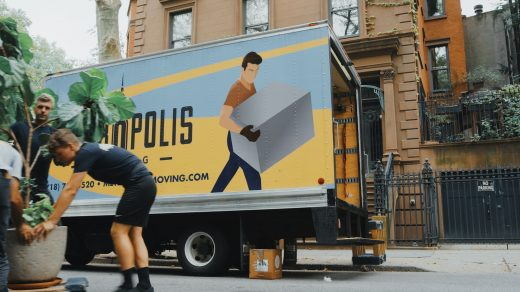 moving a house woman in blue shorts and black boots standing beside yellow and white truck during daytime