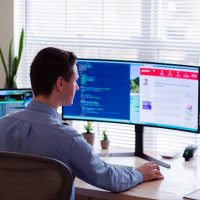 management software man in gray dress shirt sitting on chair in front of computer monitor
