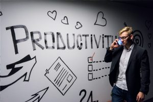 Entrepreneur needs man holding smartphone looking at productivity wall decor
