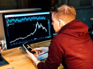 trading instruments man holding black smartphone with flat screen monitor in front