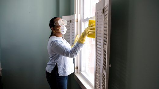 disinfection - woman in white long sleeve shirt and blue denim jeans standing beside white wooden framed glass