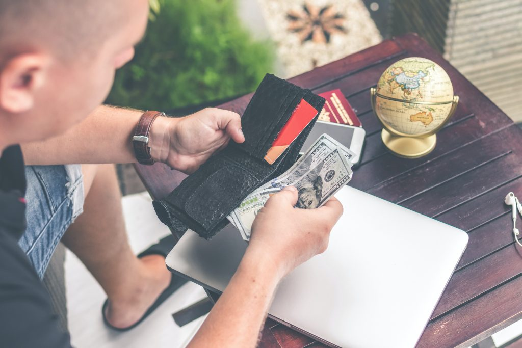 emergency loans person holding wallet and US dollar bills