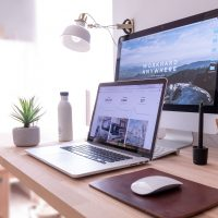 digital marketing MacBook Pro on table beside white iMac and Magic Mouse