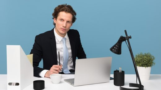 business success man sitting on chair beside laptop computer and teacup