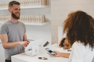 Customer Success business strategy man in grey crew-neck t-shirt smiling to woman on counter