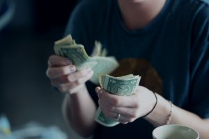 finance a business focus photography of person counting dollar banknotes