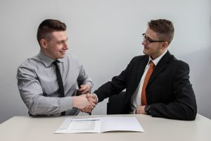 Business Consulting Partner two men facing each other while shake hands and smiling