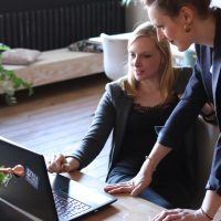 IT consulting company two woman looking at laptop screen