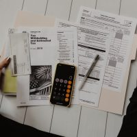 Tax-free wrapper investments person holding paper near pen and calculator