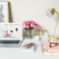 Small Business Blog MacBook Air beside gold-colored study lamp and spiral books
