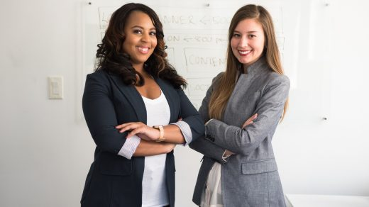 successful entrepreneur two women in suits standing beside wall