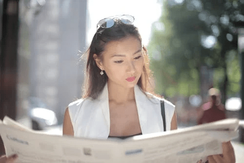 woman reading news Real Estate Agents