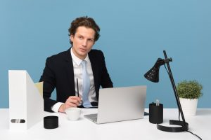 Hiring Your First Employee man sitting on chair beside laptop computer and teacup