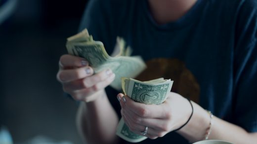 Earn Money at Home focus photography of person counting dollar banknotes