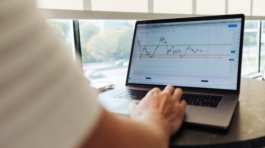 Trading problems person using MacBook Pro on table