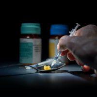 addiction person using syringe on yellow stone on spoon