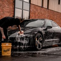 car shampoo man in black t-shirt and black pants doing water splash on black coupe during daytime