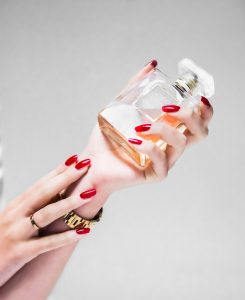 perfume person holding clear glass bottle