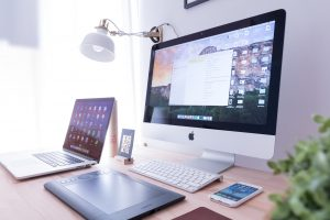 Web Applications silver iMac near iPhone on brown wooden table