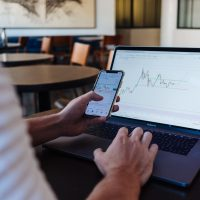 Investing in Stocks person using smartphone and MacBook Pro