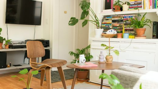 renting an apartment - brown wooden table and chair beside bookshelf