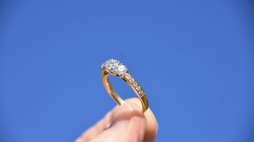 engagement ring person holding gold-colored ring