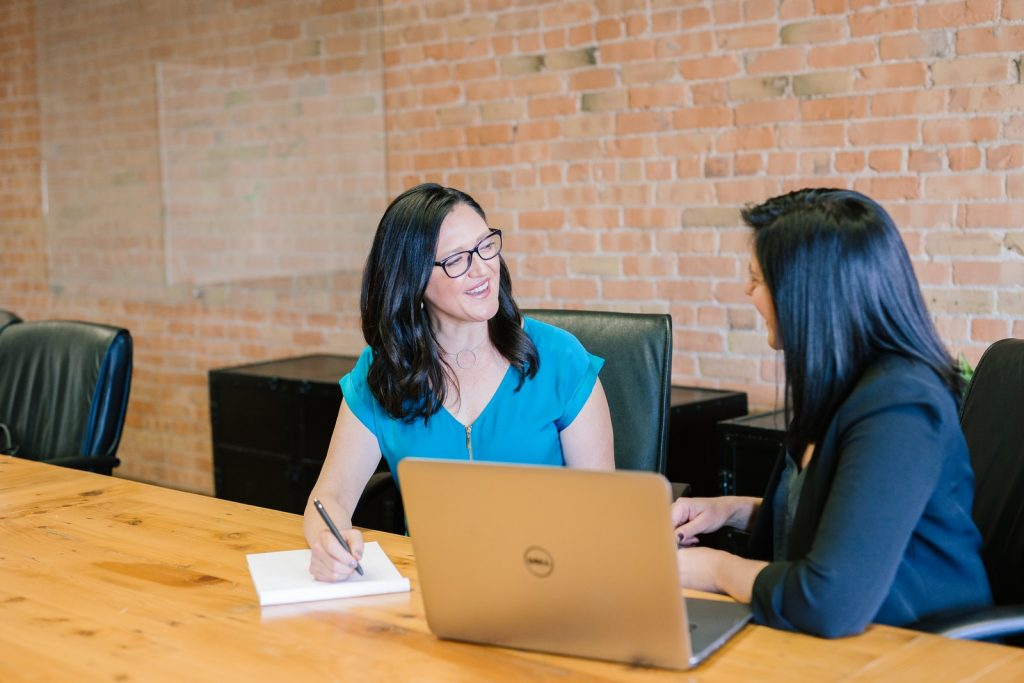 Leadership Coaching - woman in teal t-shirt sitting beside woman in suit jacket