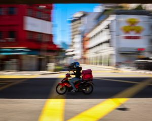 Starting a Delivery Service man in red jacket riding motorcycle on road during daytime