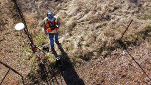 Quantity Surveyor man in orange jacket and black helmet riding red bicycle on brown dirt road during daytime