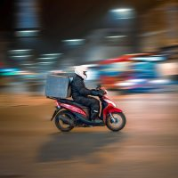 delivery business model man riding motorcycle on road during daytime