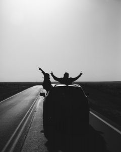 road trip grayscale photo of man riding on motorcycle on road