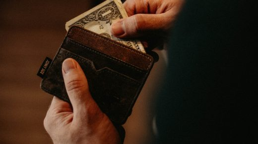 payday loans person getting 1 U.S. dollar banknote in wallet