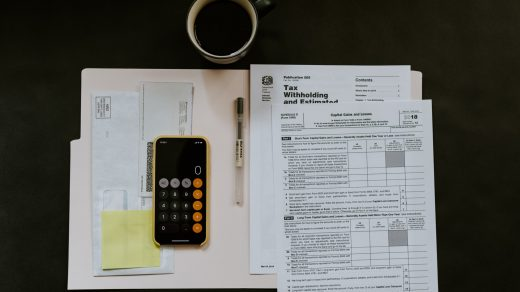 Accounting Services black Android smartphone near ballpoint pen, tax withholding certificate on top of white folder