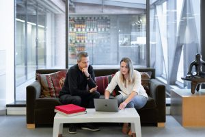 real estate agents man and woman sitting on couch using macbook