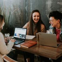 startup - three people sitting in front of table laughing together